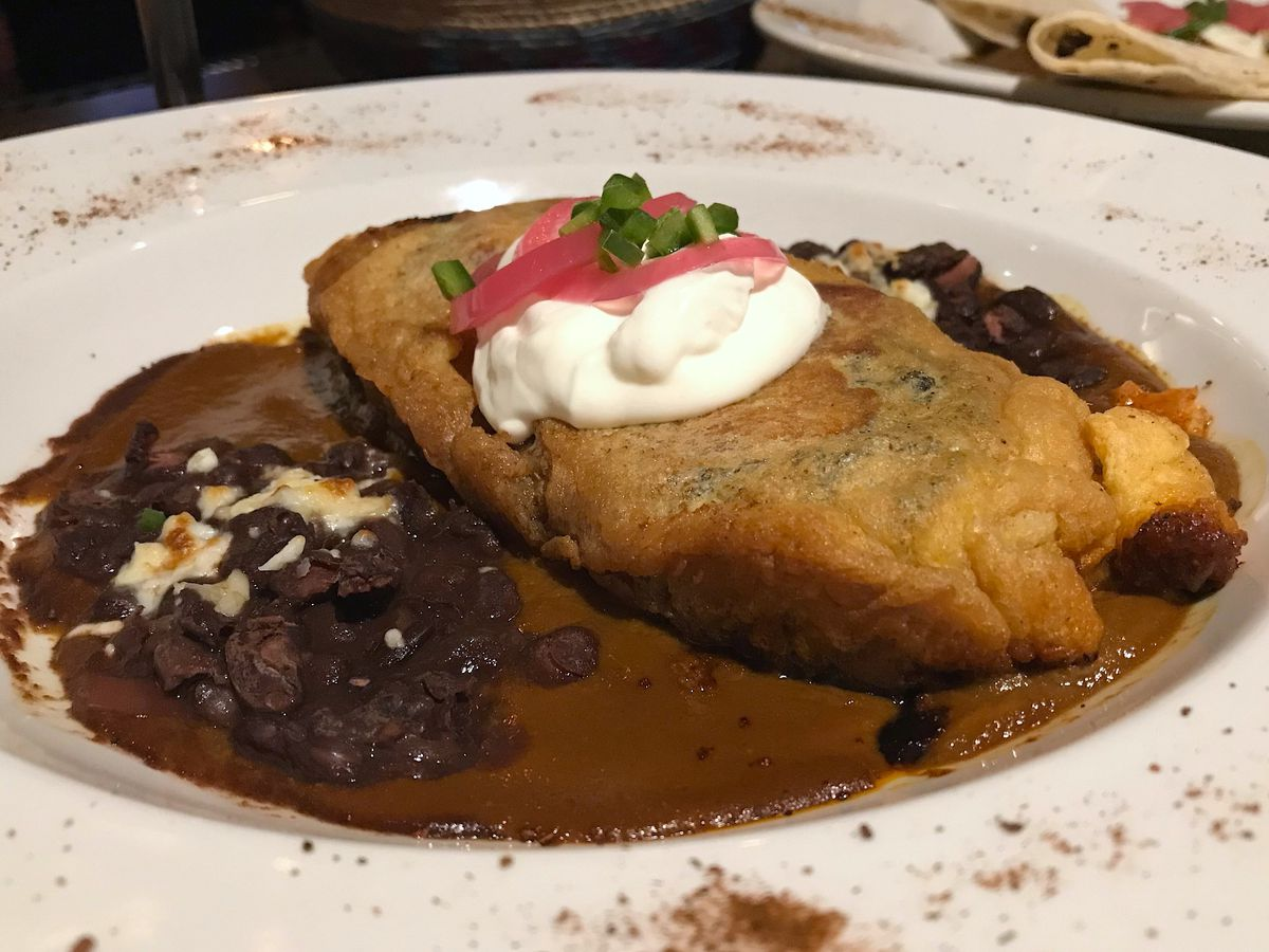 Chile relleno stuffed with black beans and cheese in mole