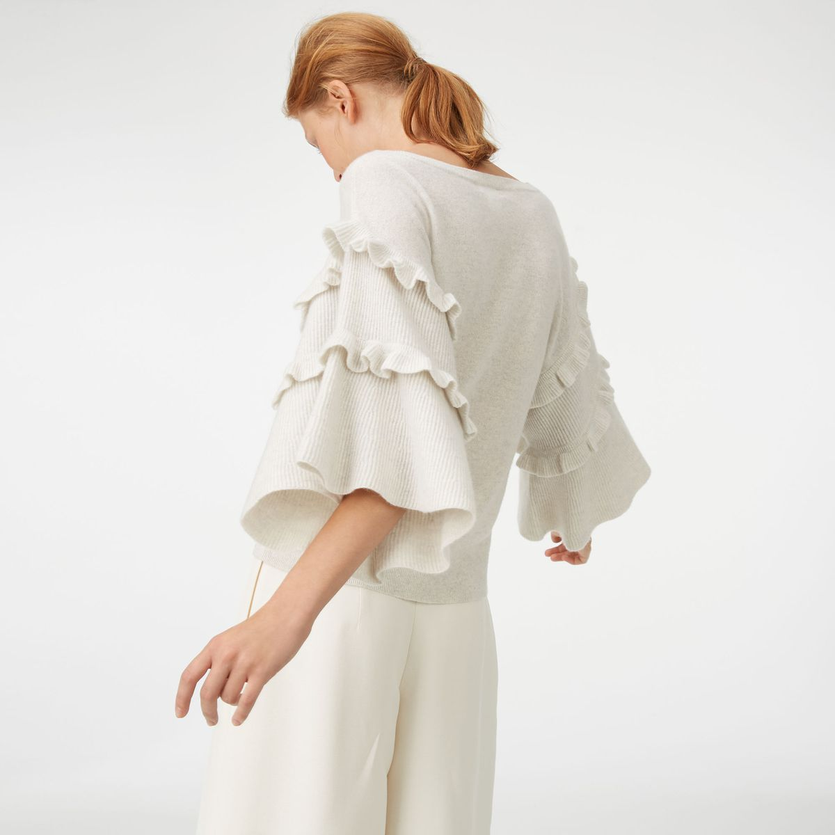 A bell-sleeved sweater with ruffles