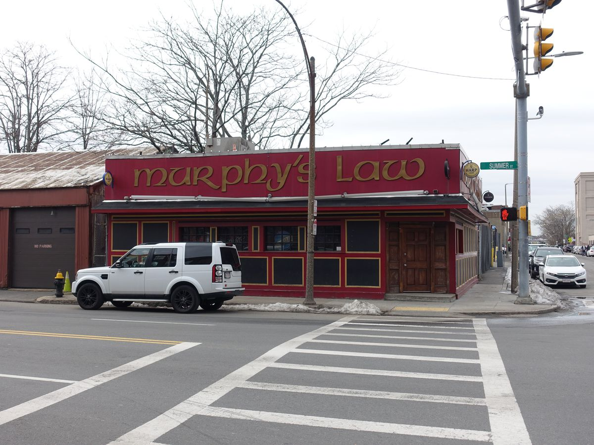 red exterior of a dive bar with murphy's law in an Irish-style gold font