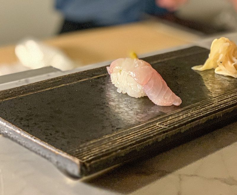 A piece of nigiri perched on a plate in front of the sushi bar.