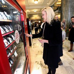 Lisa Chapman joins other visitors at the Light the World charity vending machines in the Joseph Smith Memorial Building in Salt Lake City on Friday, Dec. 15, 2017.