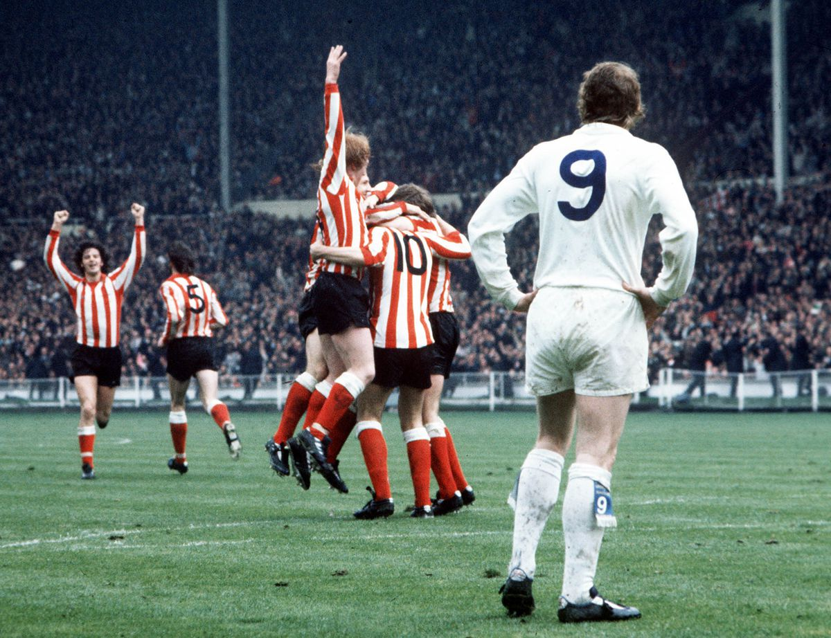 Football. 1973 FA Cup Final. Wembley Stadium. 5th May, 1973. Sunderland 1 v Leeds United 0. Sunderland+s Ian Porterfield is mobbed by teammates after scoring the games only goal to complete one of the biggest shocks in FA Cup history, watched by a dejecte