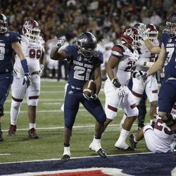 Utah State running back LaJuan Hunt (21) scores a touchdown in the second half during the Arizona Bowl NCAA college football game against New Mexico State, Friday, Dec. 29, 2017, in Tucson, Ariz. New Mexico State defeated Utah State 26-20 in overtime. (AP Photo/Rick Scuteri)