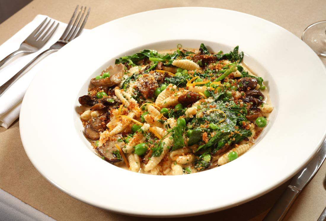 A large white bowl with a flat rim is filled with small rolls of pasta topped with peas and other greens