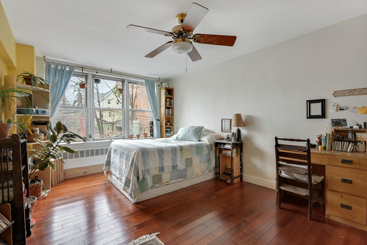 A bedroom with a tall bed, a ceiling fan, a large window, and hardwood floors.