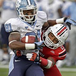 North Carolina wide receiver Roy Smith (81) gets wrestled to the ground by Louisville cornerback Jordon Paschal (22) late in the fourth quarter in an NCAA college football game in Louisville, Ky., Saturday, Sept. 15, 2012. No. 19 Louisville defeated North Carolina 39-34.