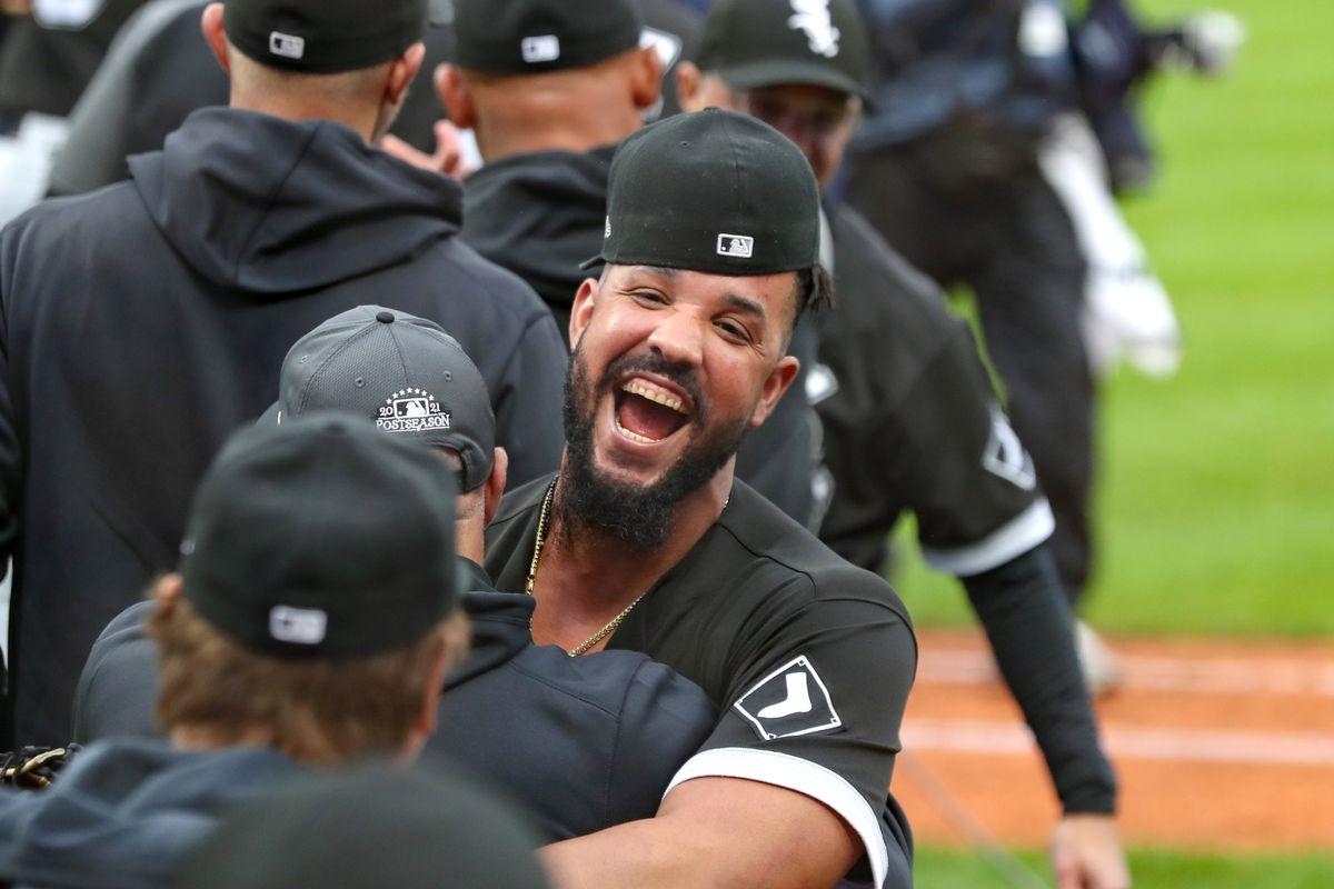 a baseball player, hat askew, hugs another baseball player