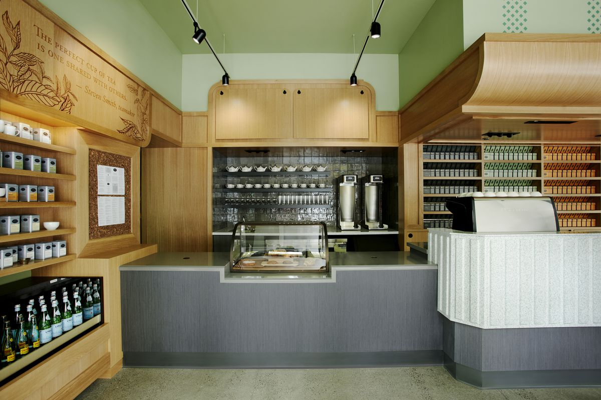 A grey counter has a pastry case, with a few teapots, mugs, canisters, and more.