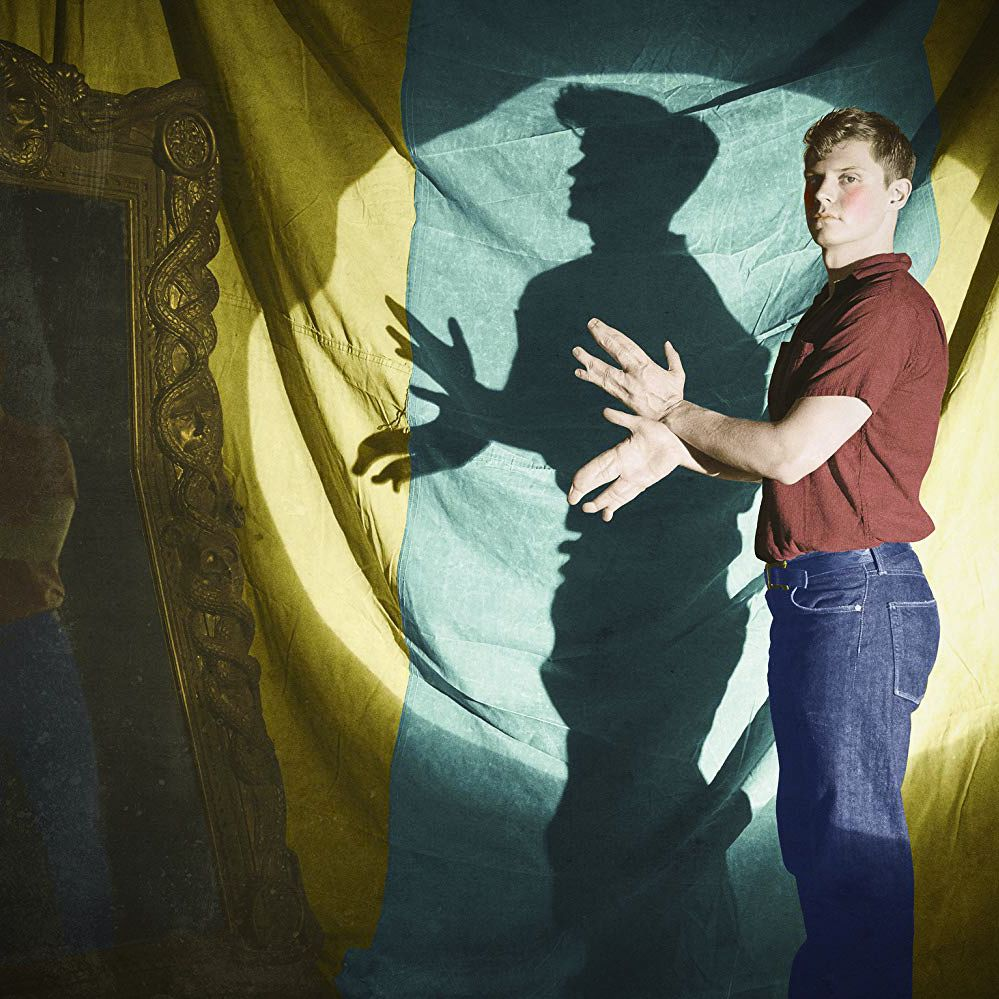 """A man holds his """"lobster claw"""" hands in front of a strong light to create a shadow."""