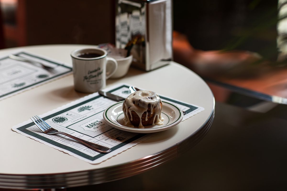 A cinnamon roll dripping with white icing on a plate next to a cup of coffee in the dimly lit dining room at Karl's.