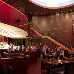 The dining room with serpentine booths in front of the kitchen at Gordon Ramsay Steak.