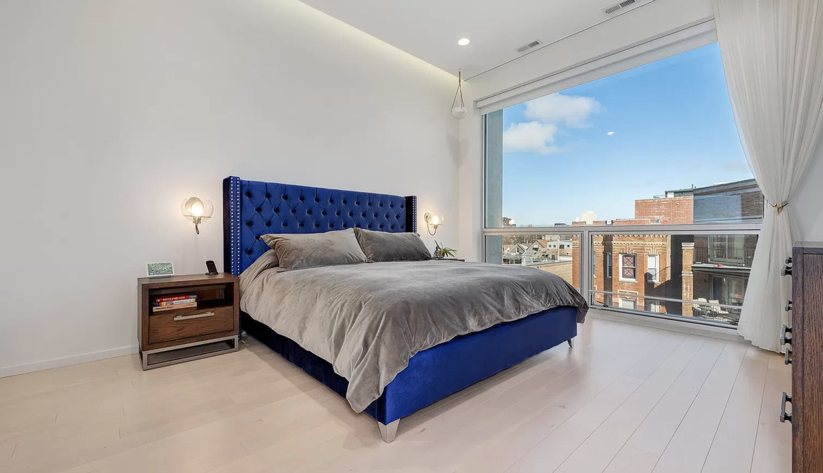 The master bedroom has a huge window, a large blue bed with a grey bedspread, and a night stand.