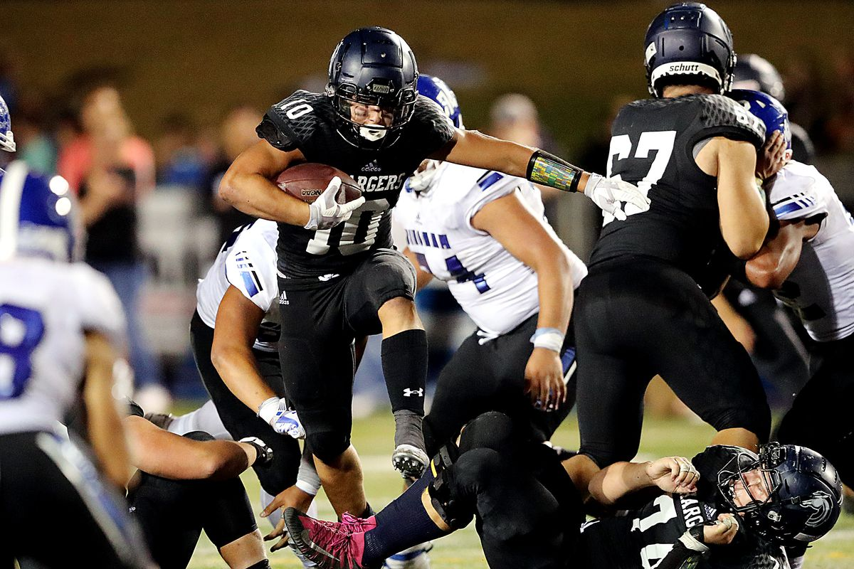 Corner Canyon's Austin Bell jumps over teammate Jackson Light during a run as their team plays Bingham in a high school football game at Corner Canyon on Friday, Aug. 30, 2019. Corner Canyon won 56-28.