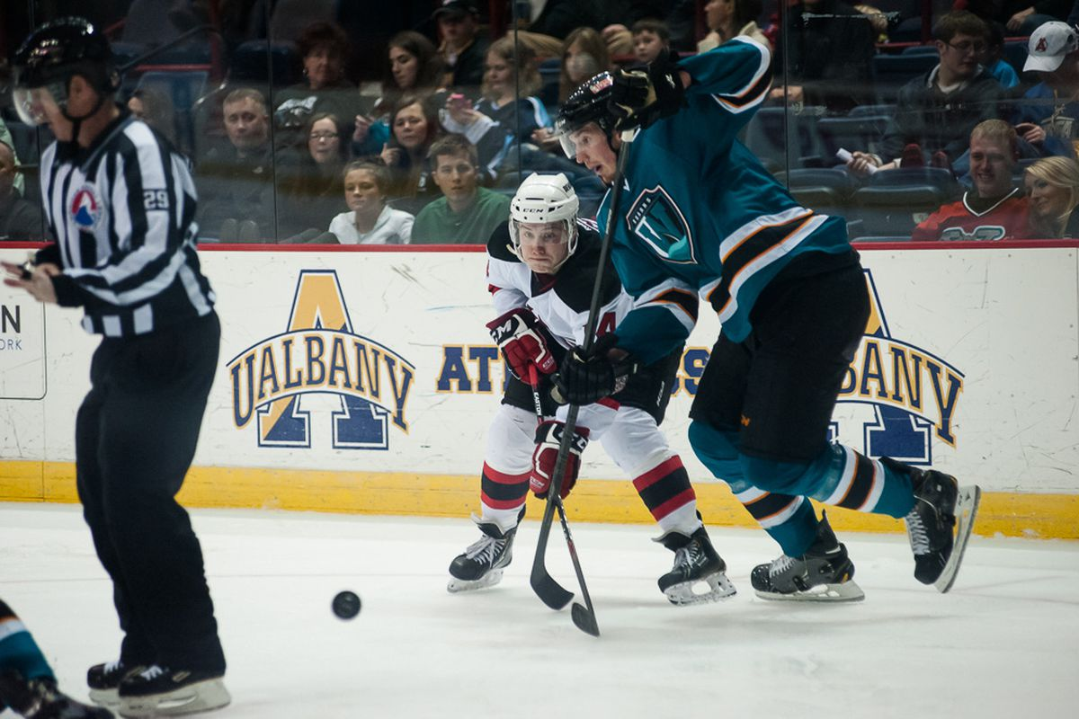Worcester Sharks forward Brodie Reid battles Albany Devils forward Reid Boucher for the puck during Saturday evening's game at the Times Union Center.