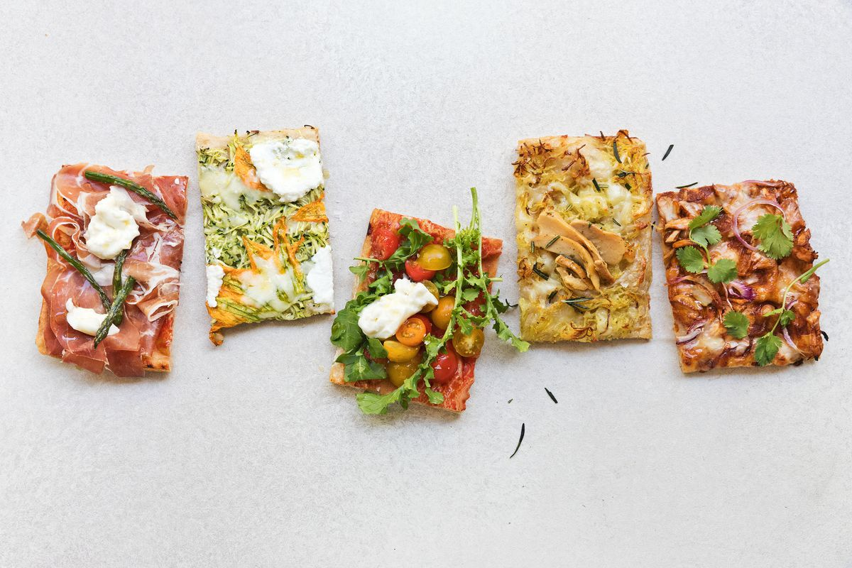 Five pieces of square, small pizza, Roman style, splayed out on a white background.