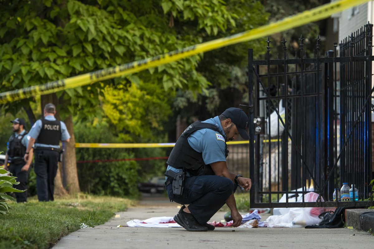 Chicago police work the scene where three people were shot including one killed in the 5400 block of South Bishop St in the Back of the Yards neighborhood, Friday, June 18, 2021.
