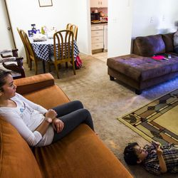 Yasimn Bilal, 13, watches TV with her siblings, Zain, 3, and Nour, 15, at their home in Millcreek on Tuesday, Sept. 8, 2015.