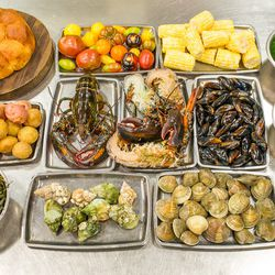 The ingredients: (top row l-r) Brioche with dill, heirloom tomatoes, corn, herb mix: chervil, tarragon, parsley. <br> (middle row l-r) New potatoes, Maine lobster, mussels, lemon. <br> (bottom row l-r) Seaweed, whelks, clams, green onion aioli.