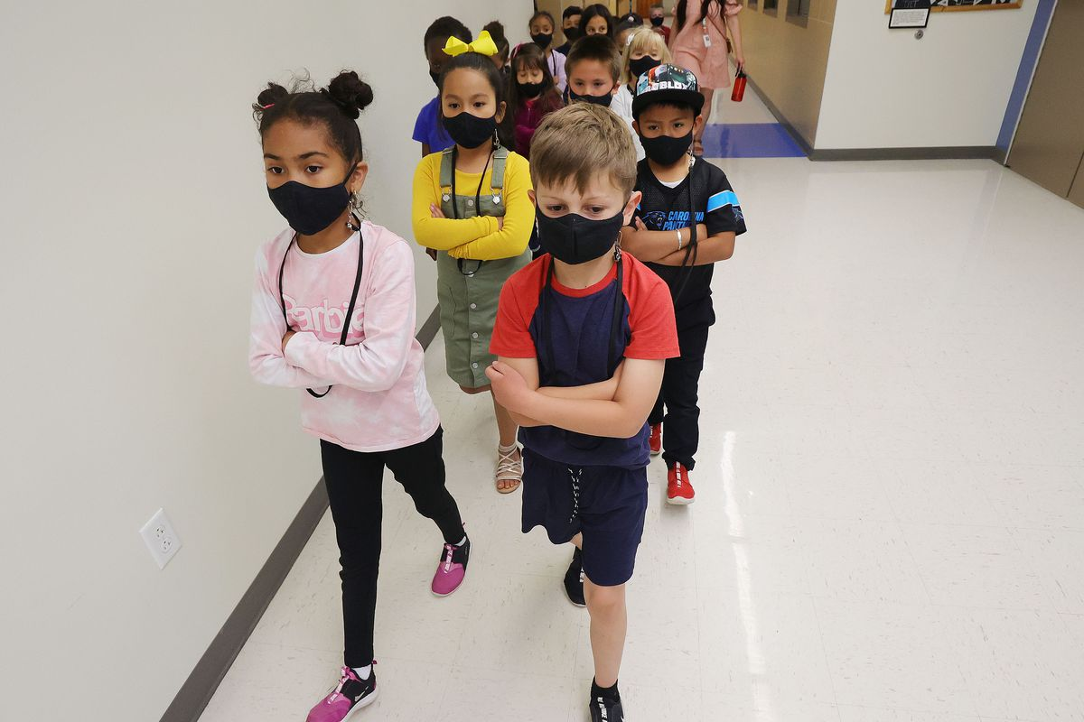 First graders and their classmates wear masks as they go to lunch at Woodrow Wilson Elementary School in Salt Lake City.