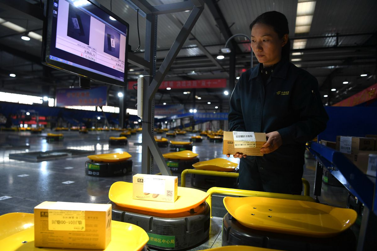 A worker in a warehouse stares at rows of circular robots that carry packages.