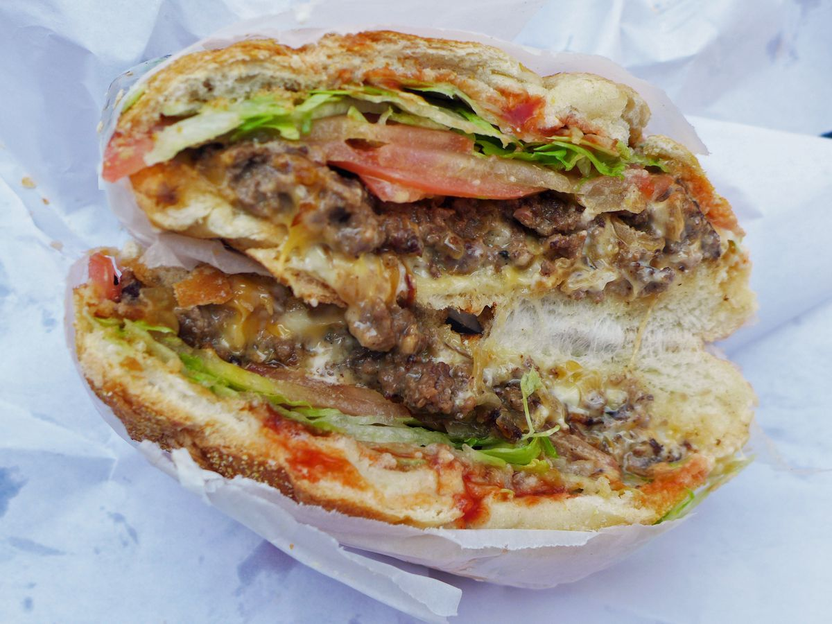 A sandwich on a roll with ground beef, lettuce, and tomatoes visible.