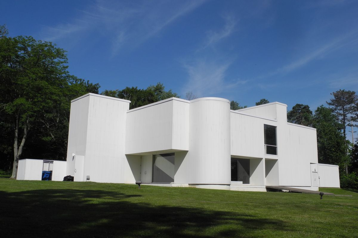 A photo of the Mansfield Art Center, a boxy white modern building set on green grass with blue skies behind it.