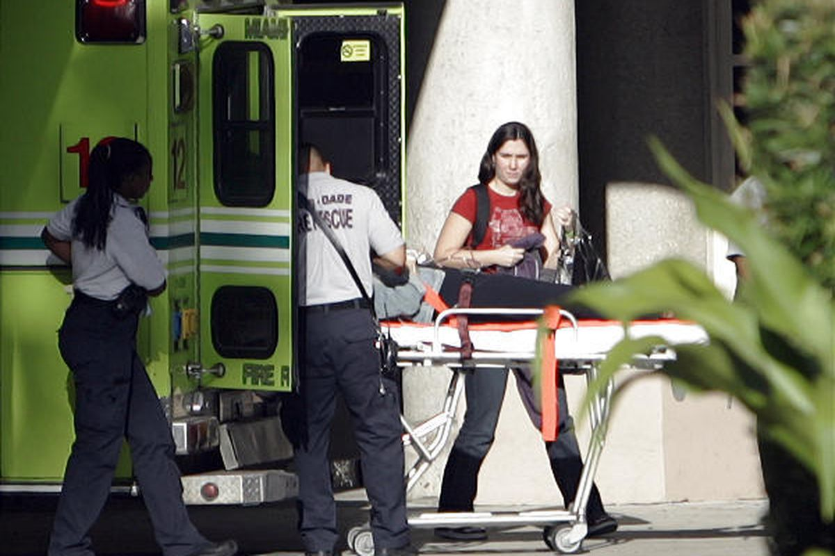 A passenger from Continental Airlines Flight 128 arrives by ambulance at a Miami hospital on Monday.