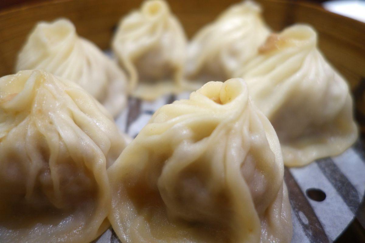 Six soup dumplings in a bamboo steam basket