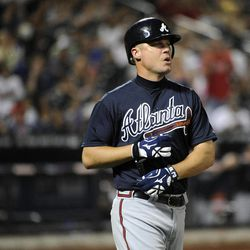 Atlanta Braves' Chipper Jones takes his batting gloves off after he lined out for the third out during the fifth inning of a baseball game on Friday, Sept. 7, 2012, at Citi Field in New York.