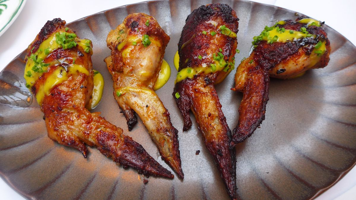 Four wings coated with spices on a metallic gray plate with ripples.