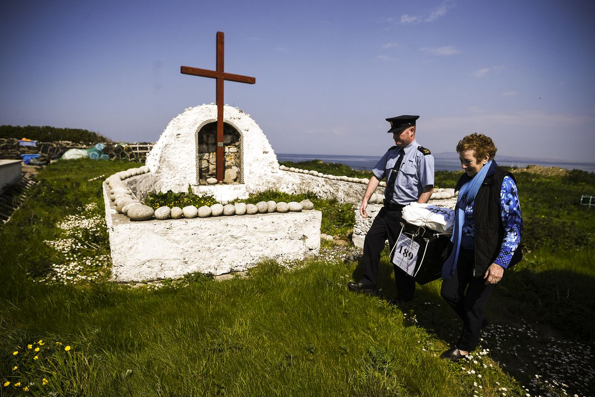 May 24: Garda Alan Gallagher and Presiding Officer Carmel McBride carry a polling box, used, a day early, by the few people that live on the island of Inishbofin in Donegal, Ireland. Ireland voted on a referendum to decide whether or not to abolish the 8t