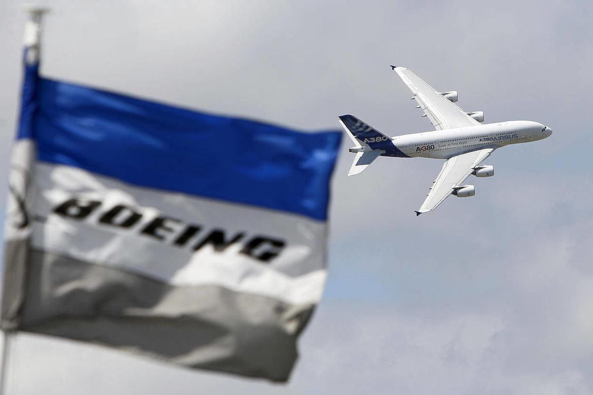 FILE - The June 25, 2011 file photo shows a Boeing flag fluttering as an Airbus A380 flies past during a demonstration flight at the 49th Paris Air Show at Le Bourget airport, east of Paris. The European Union seeks some US$ 12 billion in sanctions agains