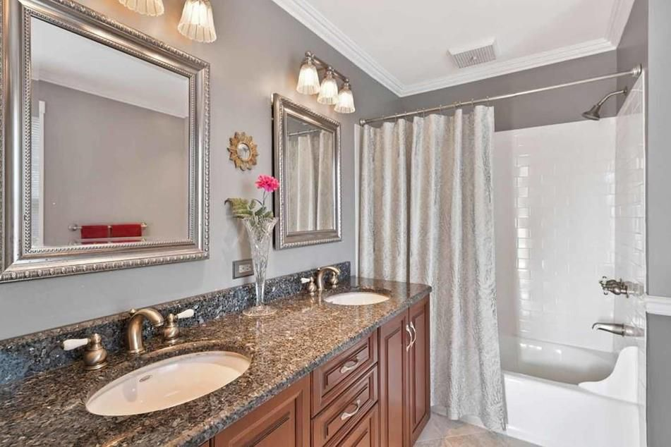 A bathroom with dual vanities and two mirrors.