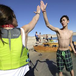 Keri Ostergaard-Welch, a teacher of the visually impaired at the Utah Schools for the Deaf and the Blind Ogden campus, high-fives Casey McKinnon as they take a break from training at Lake Powell on Saturday, March 27, 2021. McKinnon is a 16-year-old hearing impaired student from Benjamin, Utah County. They are part of the school's yacht club, which is training for the SEVENTY48, a 70-mile human-powered boat race from Tacoma to Port Townsend, Wash. Members of the yacht club built their boat for the race by hand.