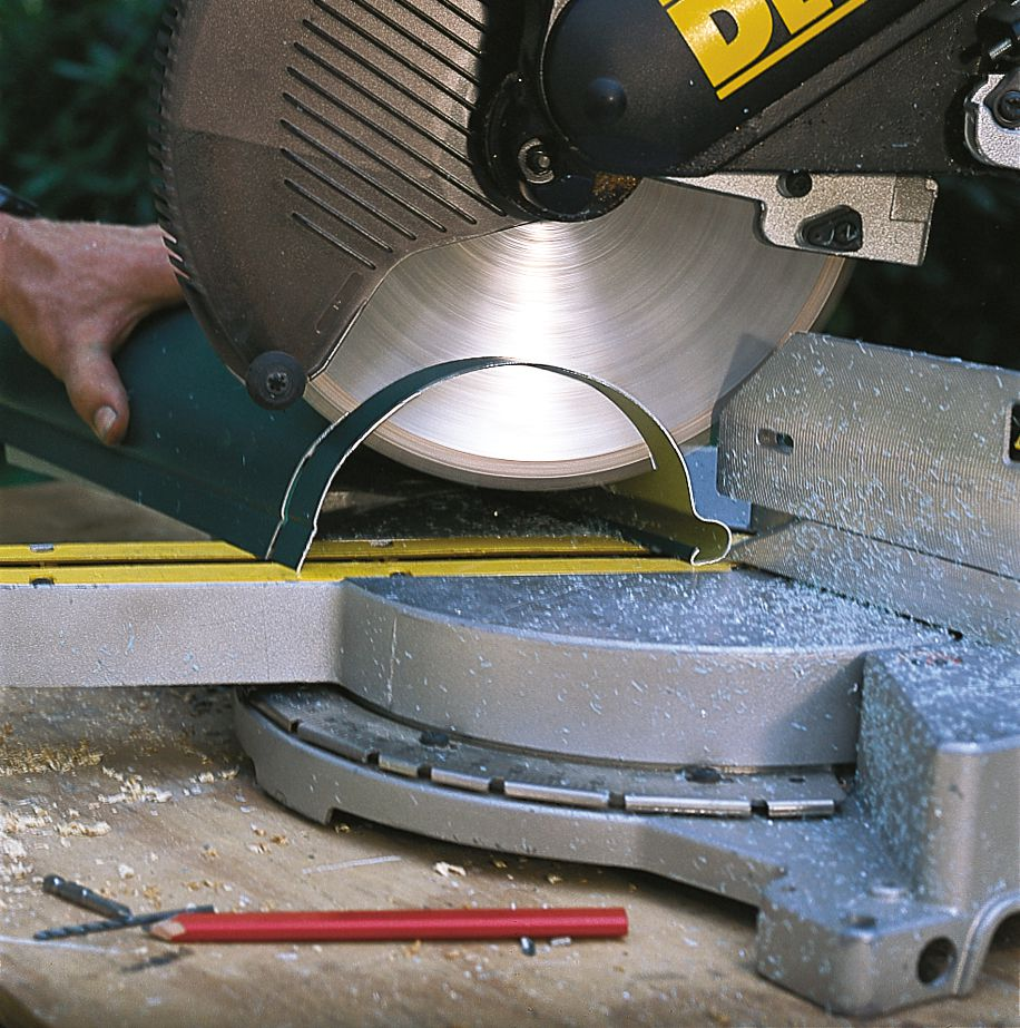 Man Cutting Gutter Section To Length With Hacksaw