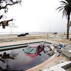 A car is partially submerged in the swimming pool of a home destroyed by Hurricane Katrina in Biloxi, Miss. The hurricane devastated the area on Monday.