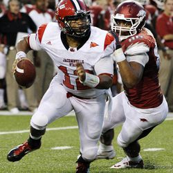 Jacksonville State quarterback Marques Ivory (12) slips past Arkansas defensive end Trey Flowers (86) during the second quarter of an NCAA college football game in Fayetteville, Ark., Saturday, Sept. 1, 2012.