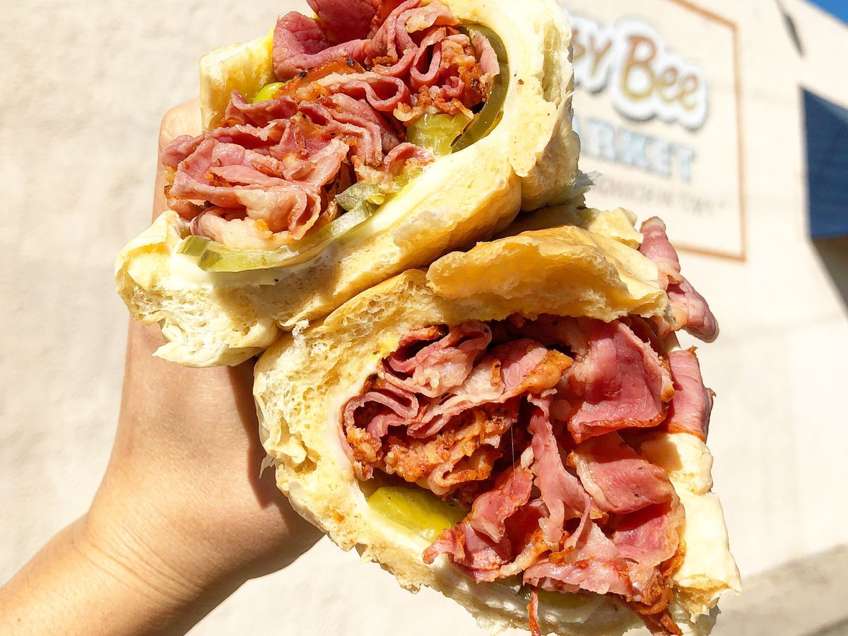 A hand holds up a pastrami sandwich that is falling apart.
