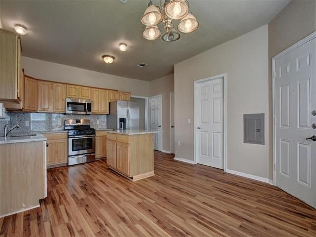 Generic 2005 open kitchen dining with new looking wood floors, counters, cabinets, etc.