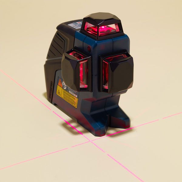 A laser level is projecting two laser lines perpendicular to each other on the floor.
