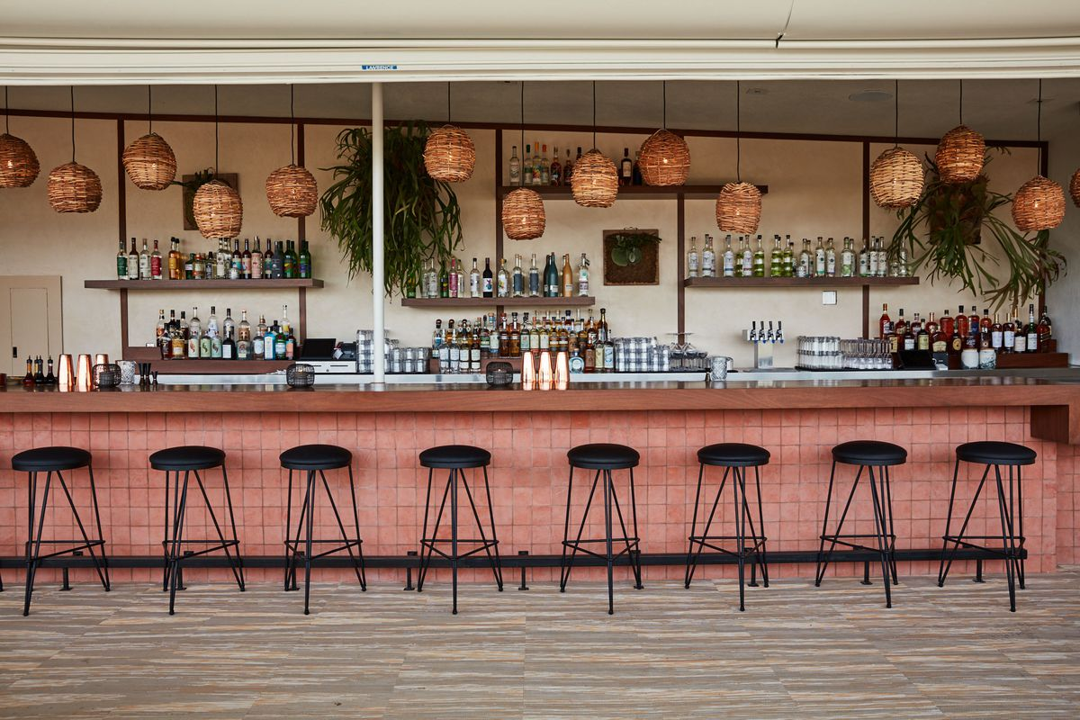 A pale pink bar area with black stools and low woven lights.