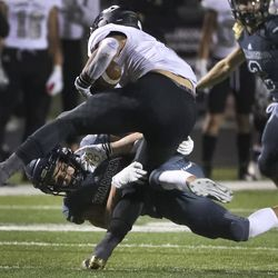 Corner Canyon's Dustin Millich wraps up Lone Peak running back Daniel Yamada during a football game at Corner Canyon in Draper on Friday, Sept. 27, 2019.