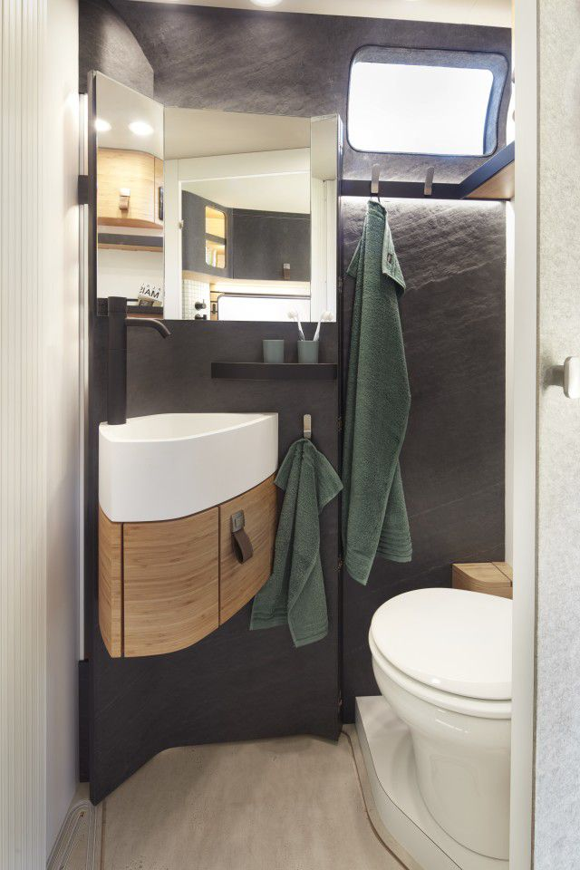 A modern bathroom with a white toilet, white and wood sink, and mirror above it.