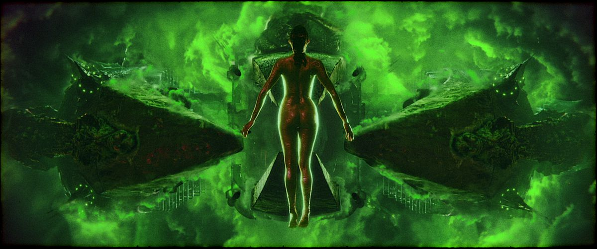 A naked female form, back to the camera, hangs in space in front of a glowing green hourglass shape made out of light