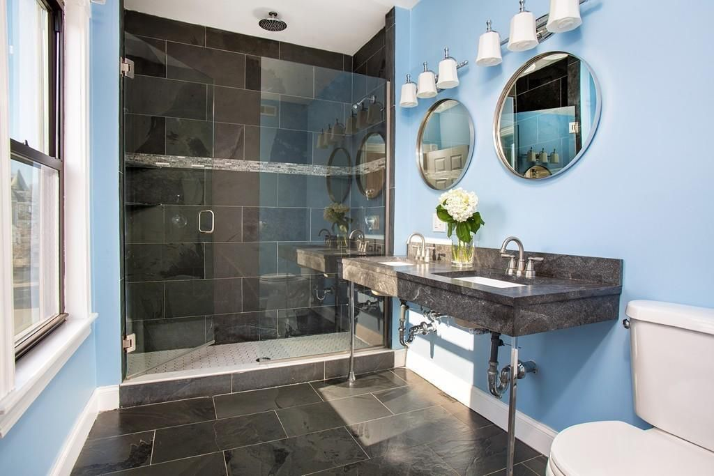 A renovated bathroom with a glass-enclosed shower, two sinks, and two oval mirrors.