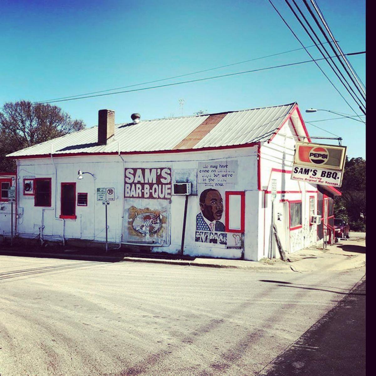 """Um prédio branco com uma placa vermelha que diz """"Sam's Bar-B-Que"""" em letras brancas ao lado de um mural de Martin Luther King Jr."""