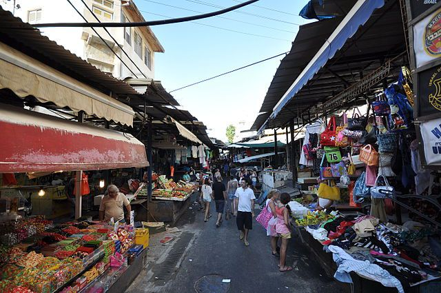 Carmel Market in Tel Aviv. The outside market is full of covered stalls with various food items and products. There are people shopping in the market.