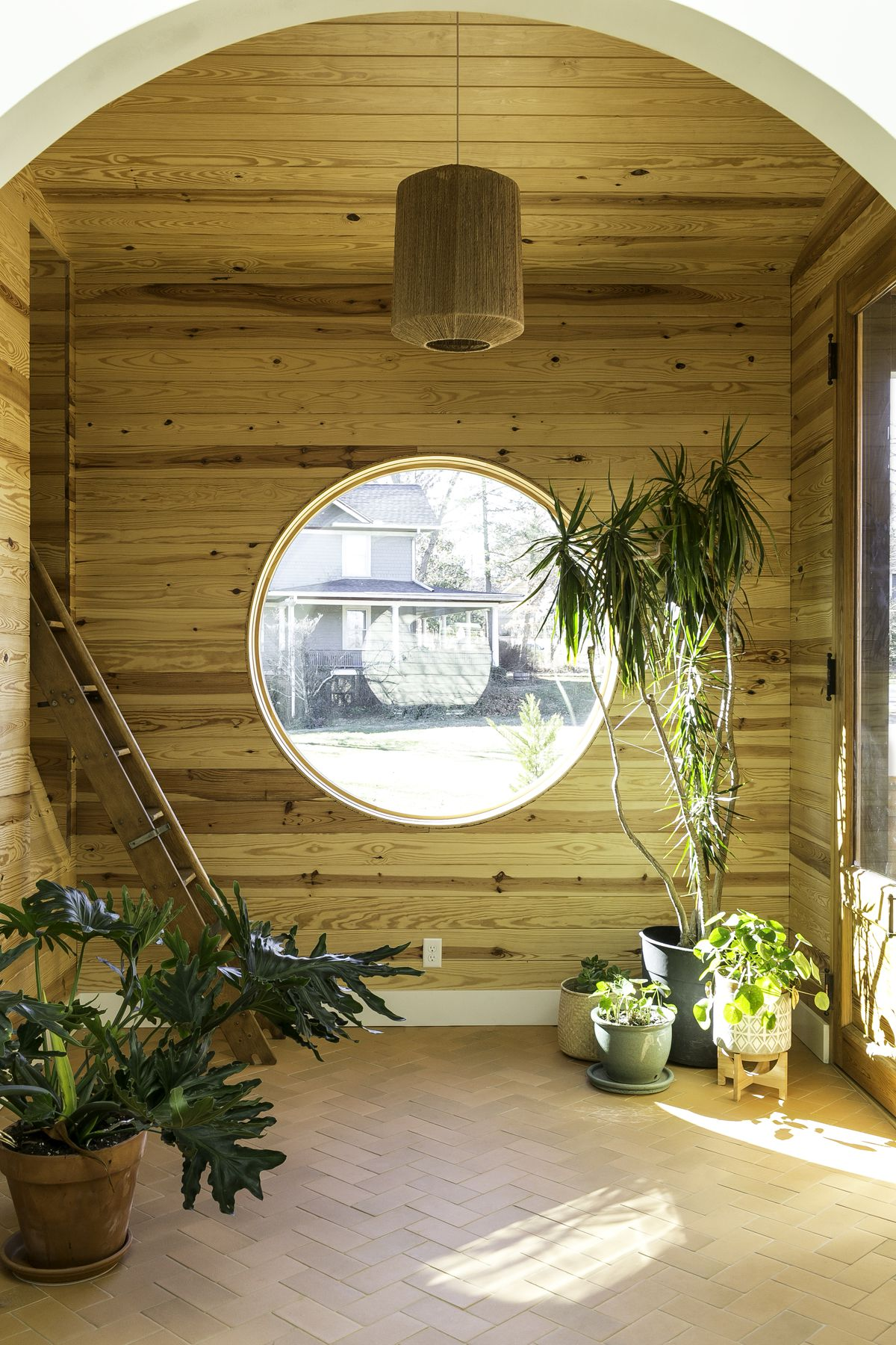 The entryway to the home, has paneled wood, a large round window, tile floor, and many potted plants.