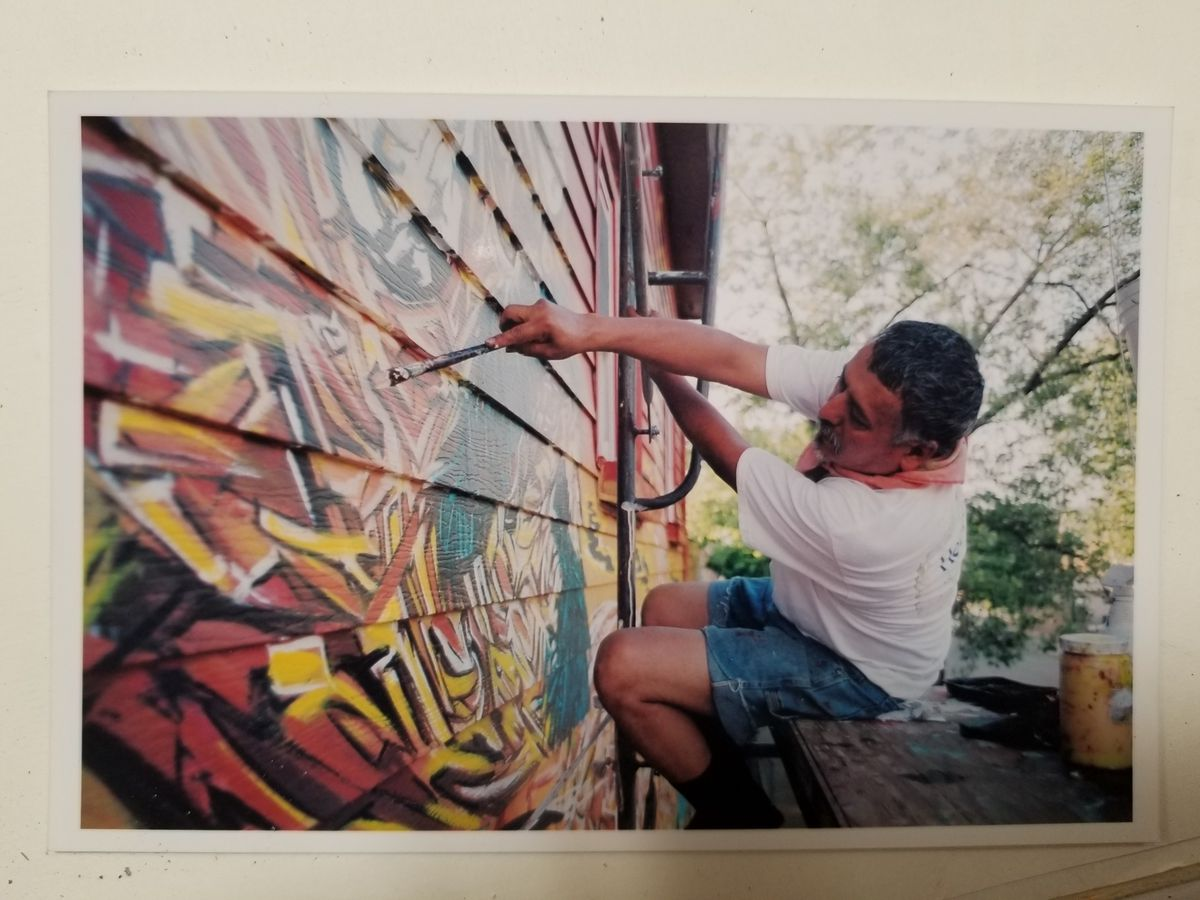 Hector Duarte painting the mural that decorates his house.