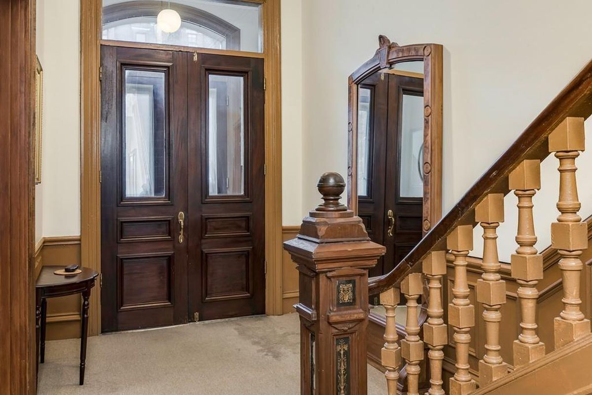 The entry foyer for a townhouse, with double front doors closed and a staircase leading from the area.